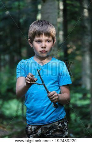 Handsome boy with makeshift slingshot in summer forest