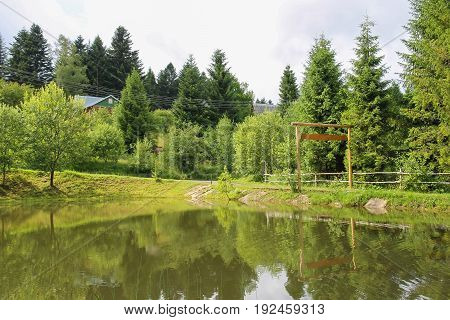 Modern cottage and old style wooden sign on shore of lake in Ukrainian Carpathians