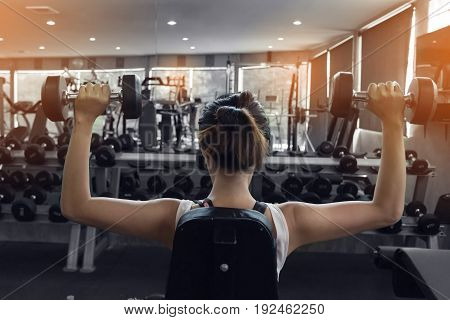 Woman Weight Lifting Dumbbell Bodybuilding In Workout Fitness Gym