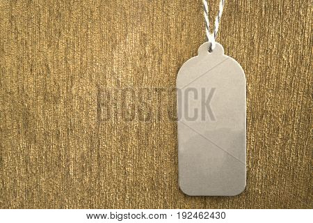Grey paper price tag hanging on brown velvet with copy space for some text advertise promotion sale concept