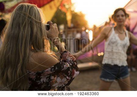 Girl friends taking photo music festival