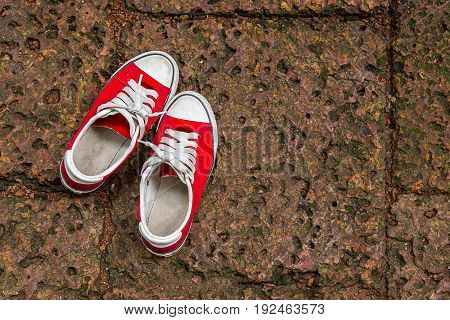 Red sneakers on a dark marble background. Footwear for outdoor activities. Sneakers concept. Sneakers on dark floor