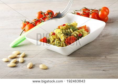 Pasta with fennel pesto almonds and cherry tomatoes on complex background