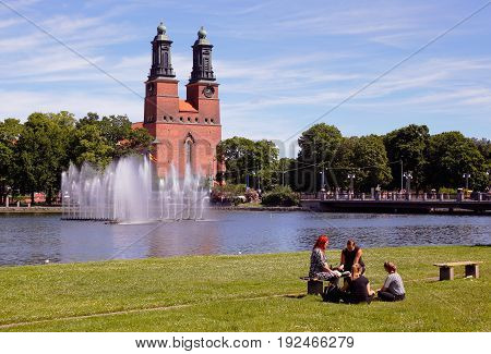 Eskilstuna Sweden - June 19 2017: A group of four people sitting in the park at the waterfront in downtown Eskilstuna with the Klosters church in the background.