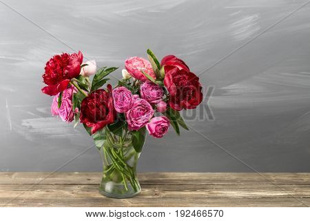 Red peonies and garden roses in vase on wooden floor and bokeh background - retro styled photo. soft focus. close-up