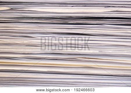 Stack of files full of documents signifying concepts such as work and stress and business objects.