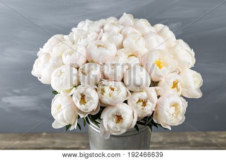 White peonies in vase on wooden floor and bokeh background - retro styled photo. soft focus. close-up