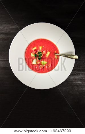 An overhead photo of a plate of gazpacho soup with slices of tomato, cucumber, and onion, with parsley leaves, on a dark background with a place for text