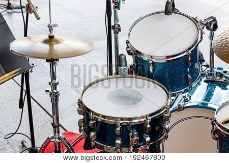 Set Of Drums, Cymbals And Microphones On Pavement Background