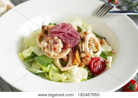 Salad with iceberg lettuce seafood and marinated red onion.