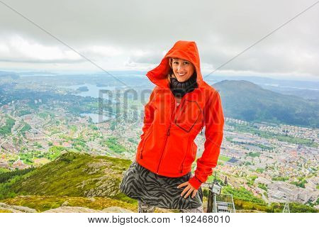 Happy tourist after hiking on Mount Ulriken. Norwegian tourism highlight. Bergen city skyline in Norway. Traveler woman in North Europe. Scenic norwegian landscape and popular landmark.