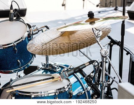 Blue Drum Set With Two Wooden Drumsticks On It. Musical Instruments On Stage Ready For The Gig.