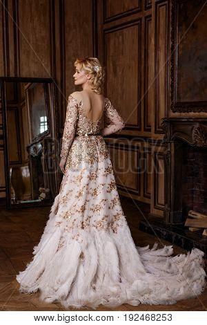 Beautiful woman in golden dress in retro style