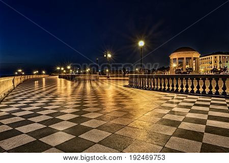 Livorno, Tuscany, Italy: promenade Mascagni Terrace at night, an elegant square on the coast with black and white checkered floor columned bannister and a round gazebo