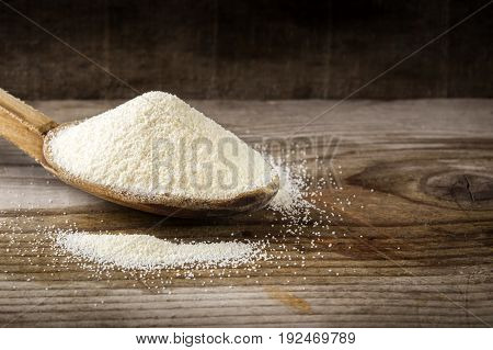 Organic semolina or couscous wheat in wooden spoon on wooden rustic background.