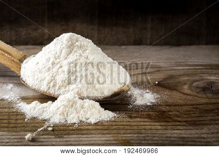 Organic wheat flour in wooden spoon on wooden rustic background.