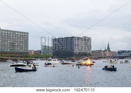 Copenhagen, Denmark - June 23, 2017: A bonfire in the harbor for the traditional midsummer celebration. Spectators in boats watching the event.