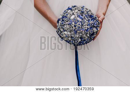 blue wedding bouquet in hands of bride isolated