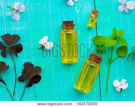Bottle Of Essential Oil With Fresh Herbal Sage, Setup With Flat Lay On Blue Wooden Table. Alternativ