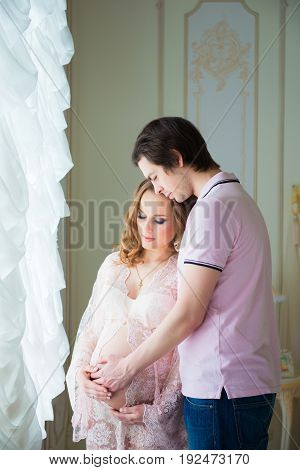 Beautiful couple, a pregnant young woman and a man, hugging with love, in the home interior.