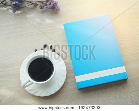 wood office table with hot black coffee cup dries purple flower and blank screen blue book. view from front office table.