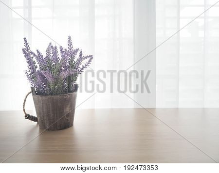 wood table with free copy space for text beautiful of purple lavender flower on pot and white drape texture background view from front wood table.