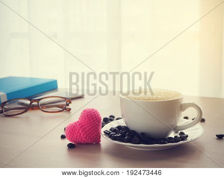 wood office table with cup of latte coffee and pink heart shape sign on blurry white drape texture background view from front wood table.