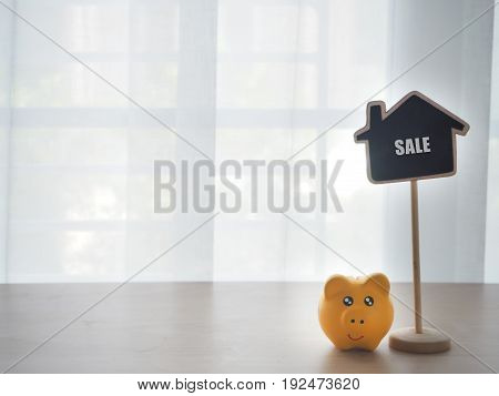 wood table with yellow piggy bank and sale text on house shape sign concept of house for sale and rent view from front wood table.
