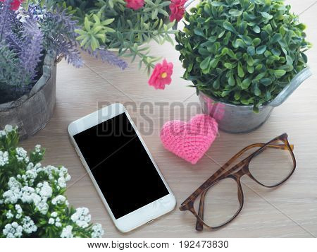 wood table with blank screen for text on smartphone tablet cell phone pink heart shape sign modern eyeglasses and beautiful flower on pot view from top wood table.