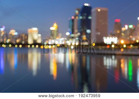 Twilight blurred bokeh office building with water reflection abstract background
