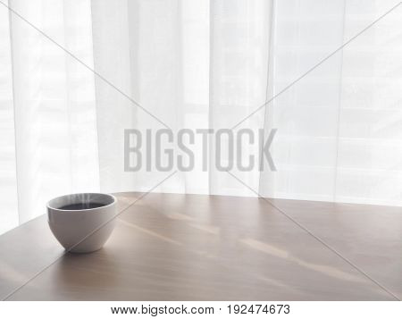 wood table with copy space for text and coffee cup of cappuccino on blurry white drape texture background view from front wood table.