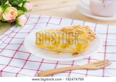Close-up image of a piece of delicious corn pie on white ceramic plate over red & white Scott pattern cloth with black tea in white cup & saucer wooden fork and small roses over wooden table