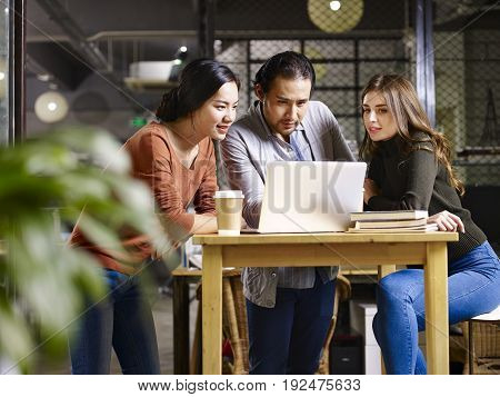 a team asian and caucasian entrepreneurs meeting in office discussing business using laptop computer.
