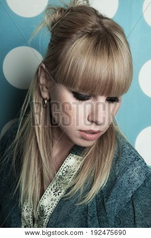Young beautiful blonde girl with long hair. Studio portrait on a blue background with white circles
