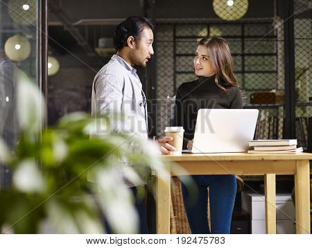 asian man and caucasian woman discussing business in office using laptop computer.