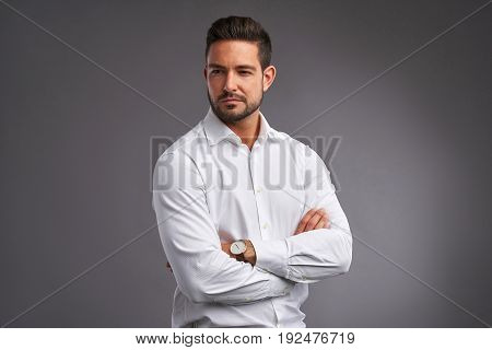 A handsome confident young man standing seriously in a white shirt.