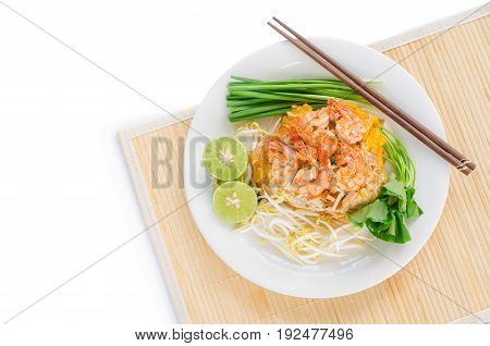 Shrimp Pad Thai stir-fried noodles (small rice noodle) wrapped with egg served with fresh bean sprout sliced lime garlic chives (or green onion) & gotu kola on white plate over place mat flat lay
