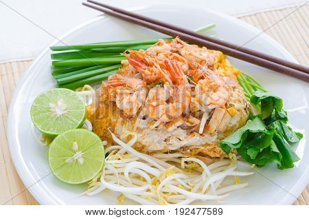Shrimp Pad Thai stir-fried noodles (small rice noodle) wrapped with egg served with fresh bean sprout sliced lime garlic chives (or green onion) and gotu kola on white plate over place mat on table