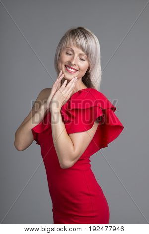 Happy girl excited. Young woman smiling very happy surprised holding head being amazed on red background. Funky young multicultural Caucasian.