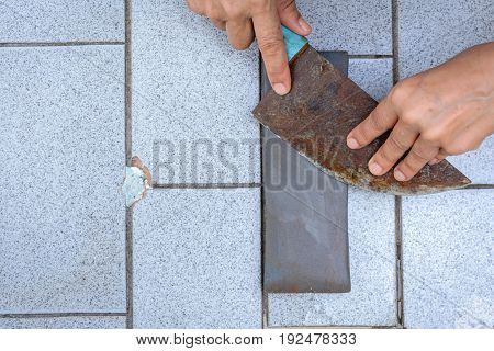 Close Up Hand With Knife Sharpener On Rock