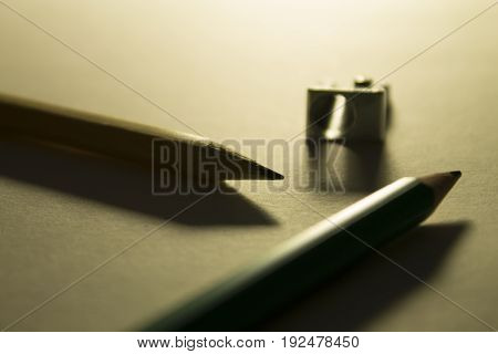 Pencils and pencil sharpener on the paper backlight