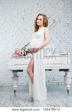 Elegant pregnant woman in a classic white dress near the white piano.