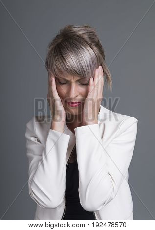 Young woman has headache, isolated on gray background.