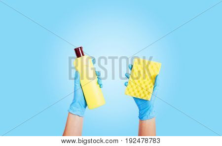 Female hands in rubber gloves hold detergent in a bottle and a sponge on a blue background