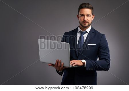 An elegant handsome young man holding a laptop and looking in to the camera
