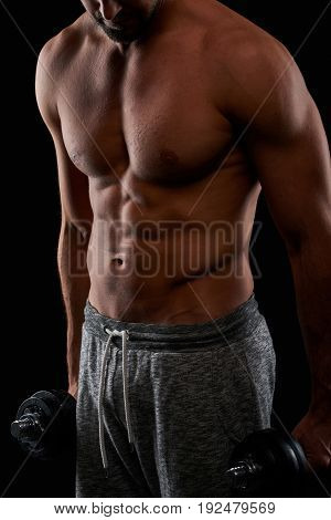 Closeup look from a young sportsman upper body while he is holding dumbbells