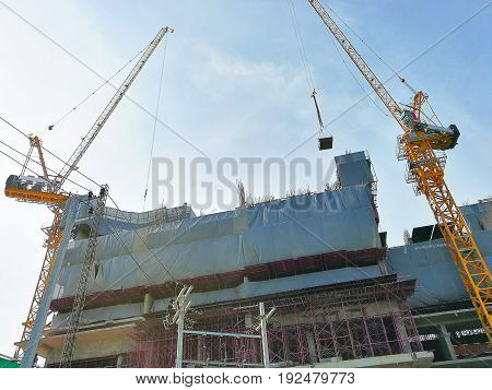 Construction cranes machine against sky background. Under construction of high-rise residential building.