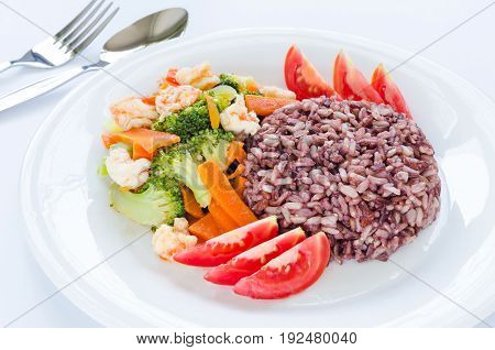 Healthy homemade dish with brown & red rice stir-fried shrimp carrot broccoli and fresh sliced tomato on white plate with silver fork and spoon on white background for good health