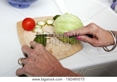 Cropped image of senior woman chopping vegetables on cutting board in kitchen
