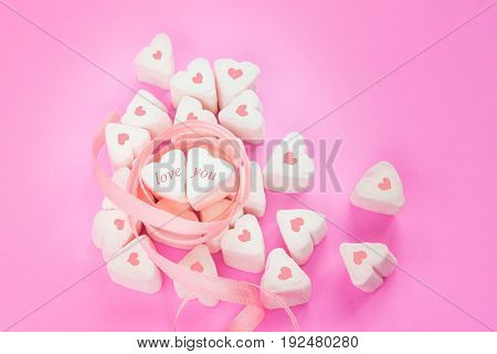 """Marshmallows candy in heart shapes with """"love"""" and """"you"""" letters surrounded with pink ribbon for Valentines day over paper background to celebrate sweet time for couples selective focus"""